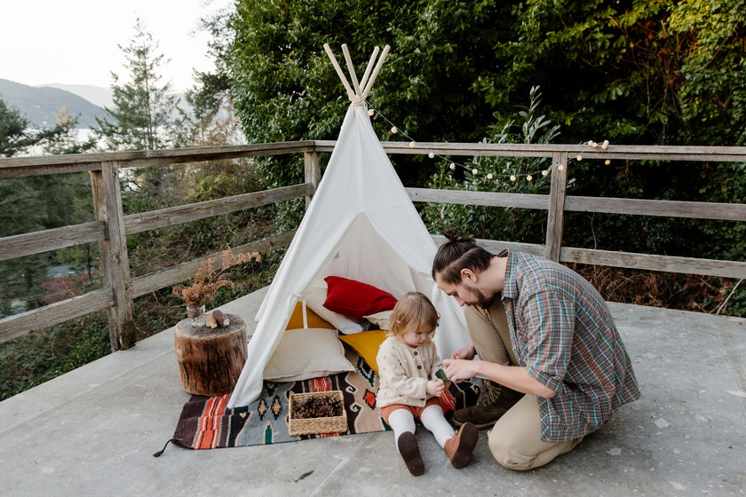 father and daughter beside a teepee